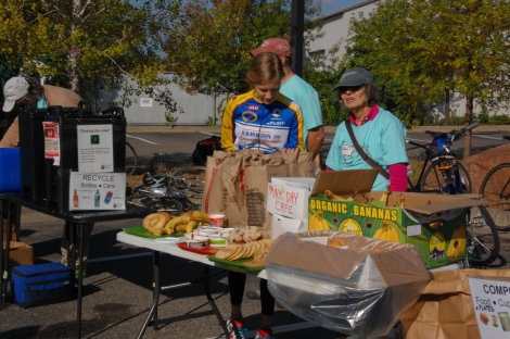 Riders and volunteers fuel up with Peace Coffee and other donated goods from May Day Café, Bruegger's Bagels, and the Seward Co-Op. Volunteer Sally Cable, at right, kept her eye on compostables at the near-zero-waste event.